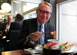 David Gonski with chop sticks and a small orange morsel.